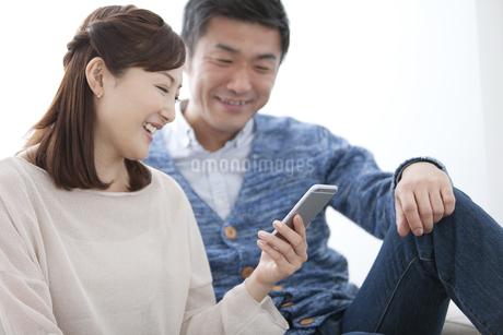 スマートフォンを見て話す中高年夫婦の写真素材 [FYI01310440]