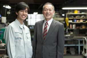 笑顔のビジネスマンと作業者の写真素材 [FYI01310485]