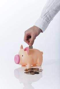 貯金箱に硬貨を入れる手の写真素材 [FYI01310492]