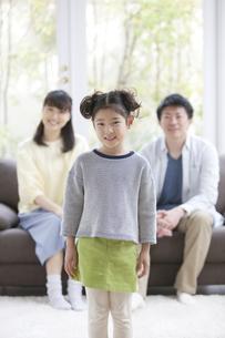 笑顔の女の子とソファーに座る両親の写真素材 [FYI01310579]