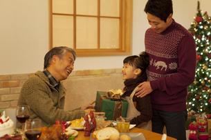 クリスマスプレゼントを渡す3世代家族3人の写真素材 [FYI01310620]