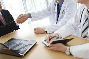 握手をするビジネスマンと医師の手元の写真素材 [FYI01310628]