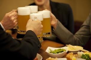 ビールで乾杯するビジネスマン4人の手元の写真素材 [FYI01310633]