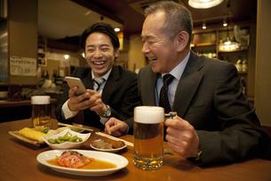 スマートフォンを見ているビジネスマン2人の写真素材 [FYI01310687]