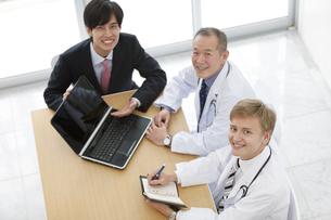 笑顔のビジネスマンと医師3人の写真素材 [FYI01310715]