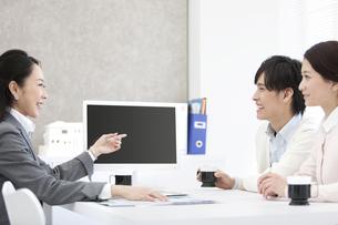 説明をするビジネスウーマンと夫婦の写真素材 [FYI01310720]
