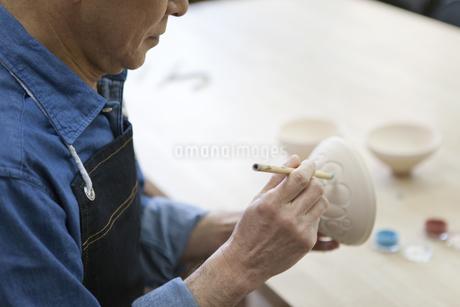 茶碗に絵を描くシニア男性の写真素材 [FYI01310746]