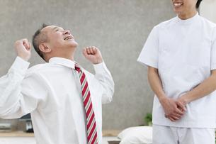 伸びをするシニア男性とマッサージ師の写真素材 [FYI01310749]
