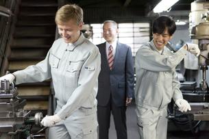 機械を操作する作業者2人とビジネスマンの写真素材 [FYI01310760]