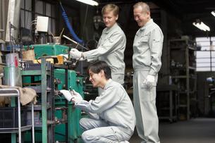 機械を操作する作業者3人の写真素材 [FYI01310789]