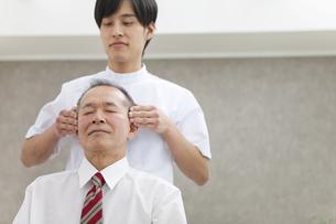 頭のマッサージを受けるシニア男性の写真素材 [FYI01310811]
