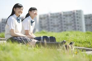 土手に座る女子校生2人の写真素材 [FYI01311043]