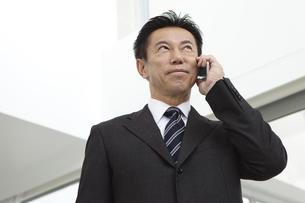 スマートフォンで電話するビジネスマンの写真素材 [FYI01311053]