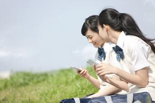 スマートフォンを操作する女子校生2人の写真素材 [FYI01311062]