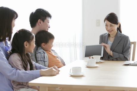 ビジネスウーマンの説明を聞く家族4人の写真素材 [FYI01311106]