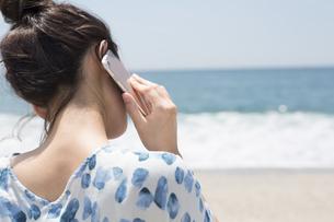 砂浜に座って電話する女性の写真素材 [FYI01311218]