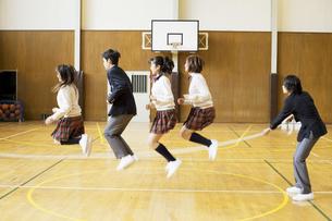 体育館で大縄跳びをする学生達の写真素材 [FYI01311393]