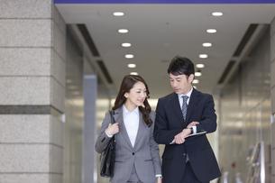 腕時計を見るビジネスマンとビジネスウーマンの写真素材 [FYI01311405]