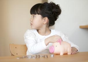 貯金箱にお金を入れる女の子の写真素材 [FYI01311417]