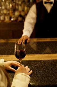 ワイングラスを持つ女性の手元とバーテンダーの写真素材 [FYI01311449]