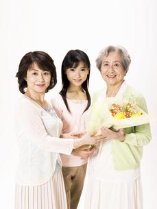 シニア女性に花束を渡す母娘の写真素材 [FYI01311496]