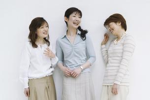 壁にもたれて立つミドル女性3人の写真素材 [FYI01311548]