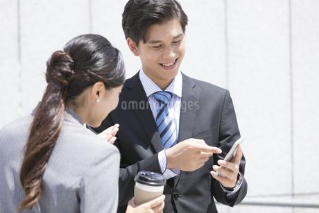 スマートフォンを見ているビジネスカップルの写真素材 [FYI01311611]