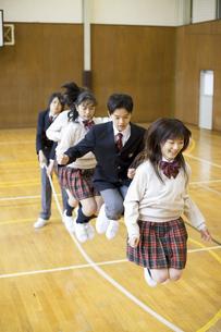 体育館で大縄跳びをする学生達の写真素材 [FYI01311734]