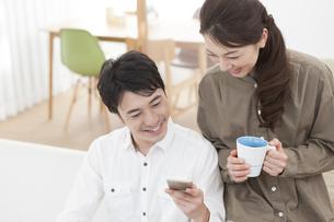 スマートフォンを見るカップルの写真素材 [FYI01311888]