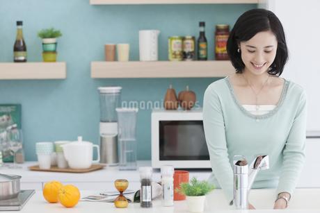 キッチンに立つ女性の写真素材 [FYI01311991]