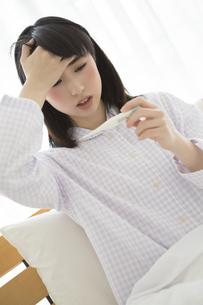 体温計で熱を測っている女性の写真素材 [FYI01312148]