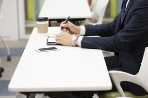 ペンと手帳を持つビジネスマンの写真素材 [FYI01312194]