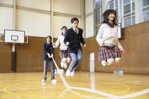 体育館で大縄跳びをする学生達の写真素材 [FYI01312329]