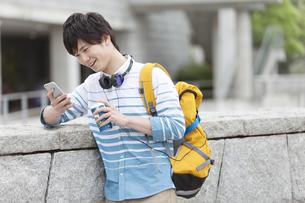 スマートフォンを見る男子学生の写真素材 [FYI01312379]