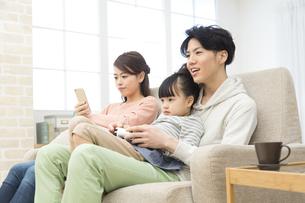 ソファーに座ってくつろぐ家族3人の写真素材 [FYI01312469]