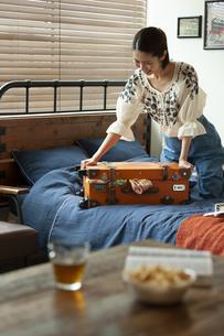 トランクを閉める笑顔の女性の写真素材 [FYI01312555]