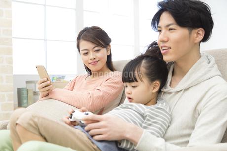 ソファーに座ってくつろぐ家族3人の写真素材 [FYI01312560]