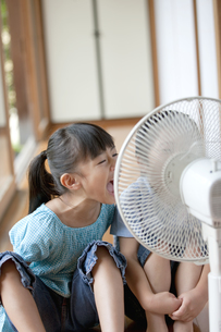 扇風機で涼むきょうだいの写真素材 [FYI01312694]