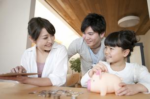 貯金箱と家族の写真素材 [FYI01312844]