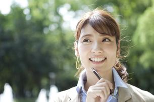 顎にペンをあてるビジネス女性の写真素材 [FYI01312938]