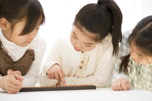 そろばんしている女の子3人の写真素材 [FYI01313023]