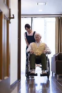 車椅子に乗るシニア男性とヘルパーの写真素材 [FYI01313246]