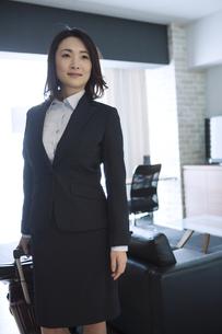ホテルの部屋でスーツケースを引くビジネスウーマンの写真素材 [FYI01313264]