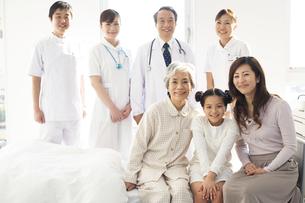 病室に集まる笑顔の家族と医師と看護師の写真素材 [FYI01313310]