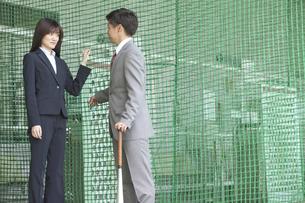 バッティングセンターにいるビジネス男女2人の写真素材 [FYI01313396]