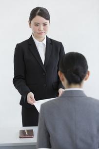 面接官に履歴書を渡す女性の写真素材 [FYI01313470]