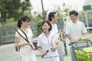 テニスコートで話す男女4人の写真素材 [FYI01313514]