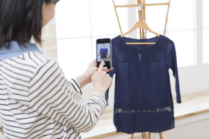 服を撮影する女性の写真素材 [FYI01313568]