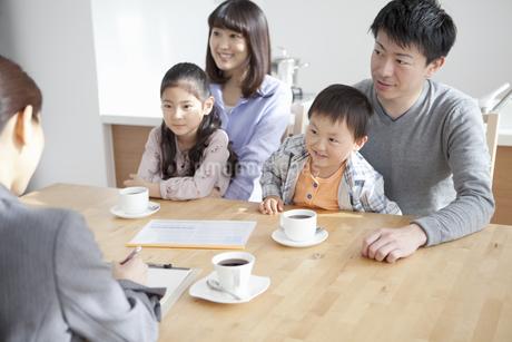 ビジネスウーマンの説明を聞く家族4人の写真素材 [FYI01313736]