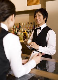 男性従業員に注文を伝える女性従業員の写真素材 [FYI01313751]